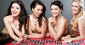 Image of the live dealers at 32Red. Four dealers stand behind a roulette table.